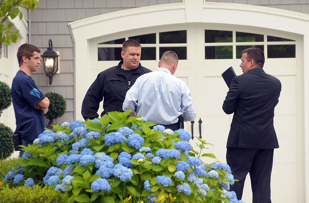 . Police investigators work outside the home of former New England Patriots football player Aaron Hernandez Thursday, June 27, 2013, in North Attleboro, Mass.  A judge on Thursday denied bail for the former NFL player, who is charged with first-degree murder in the shooting death of a friend. (AP Photo/The Attleboro Sun Chronicle, Mark Stockwell)