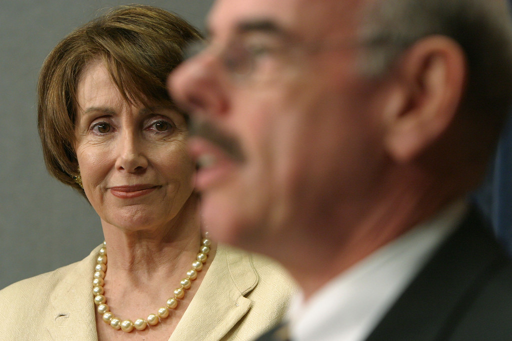 . U.S. House Democratic Leader Nancy Pelosi (D-CA) listens as Rep. Henry Waxman (D-CA) speaks during a news conference on Capitol Hill June 23, 2004 in Washington, DC.   (Photo by Matthew Cavanaugh/Getty Images)