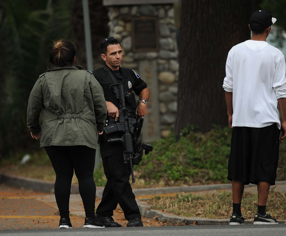 . Ontario Police officers search for an allegedly armed man in the 100 block East Harvard Place near Euclid Avenue Sunday in Ontario. (LaFonzo Carter/Staff Photographer)