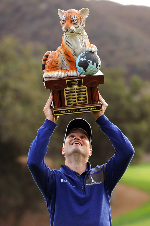 . Zach Johnson hoists the tournament trophy after defeating Tiger Woods in a playoff hole in the final round of the Northwestern Mutual World Challenge golf tournament at Sherwood Country Club, Sunday December 8, 2013, in Thousand Oaks, Calif.(Andy Holzman/Los Angeles Daily News)