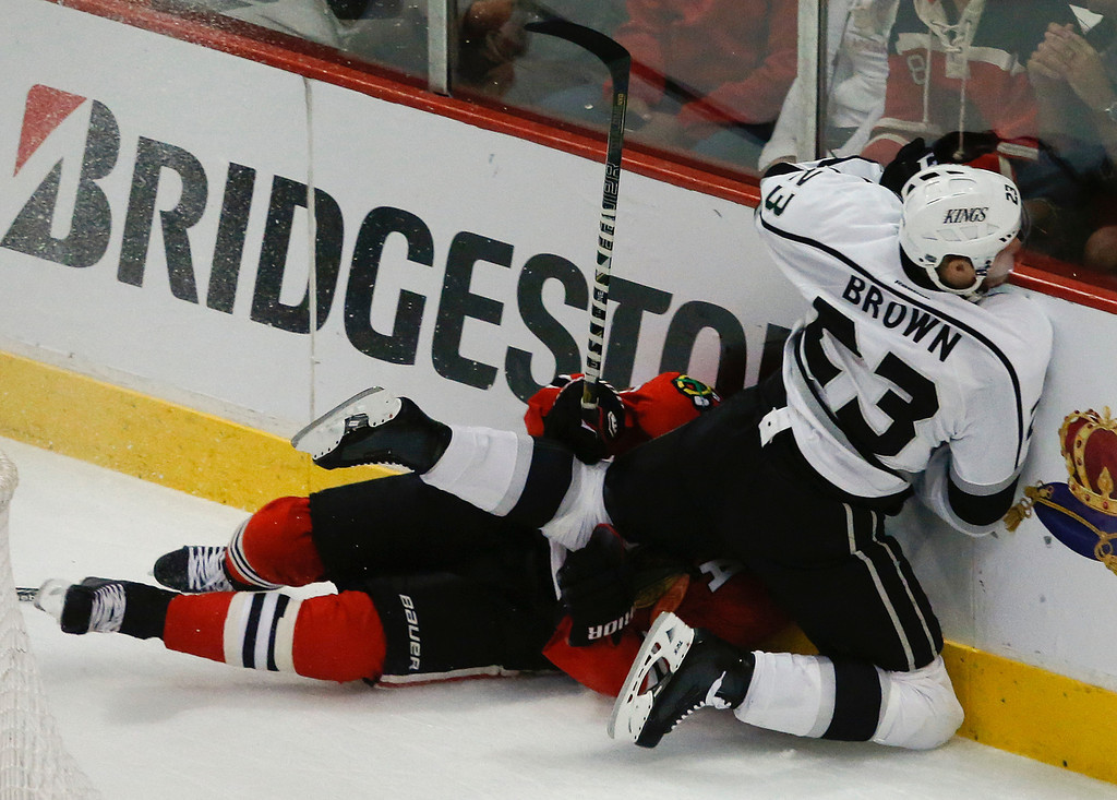 . Los Angeles Kings right wing Dustin Brown (23) collides with Chicago Blackhawks defenseman Duncan Keith (2) against the boards during the first period in Game 2 of the NHL hockey Stanley Cup Western Conference finals Sunday, June 2, 2013 in Chicago. (AP Photo/Charles Rex Arbogast)