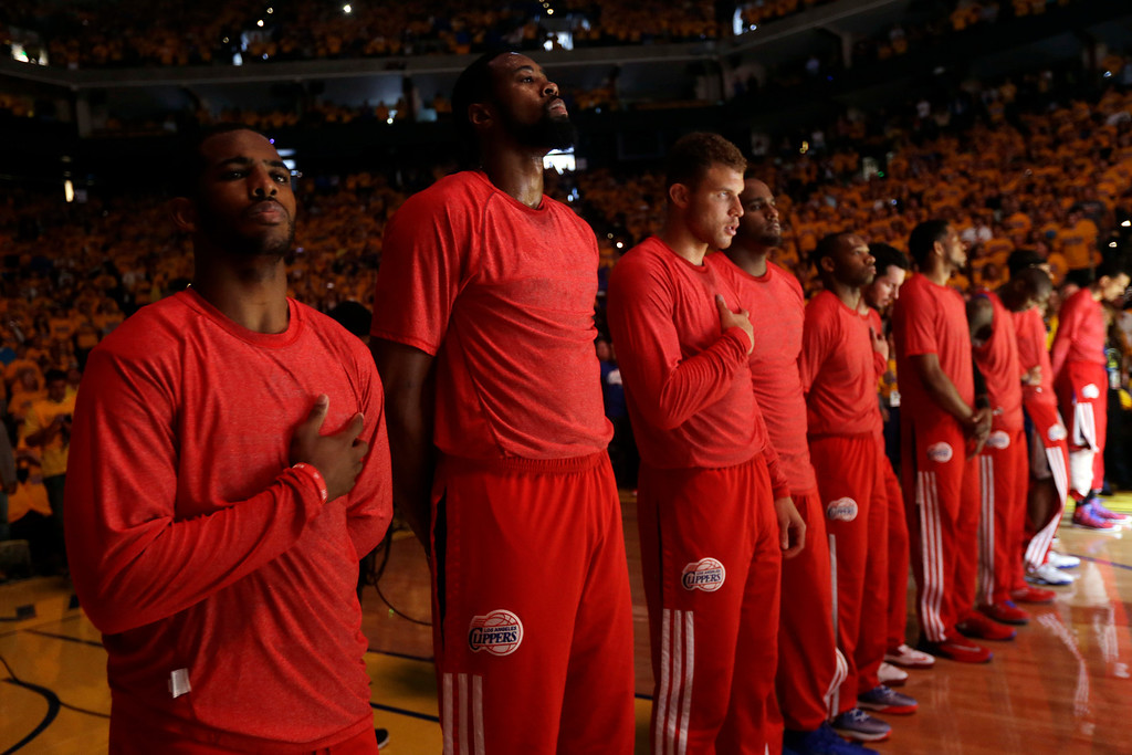 . Members of the Los Angeles Clippers listen to the national anthem before Game 4 of an opening-round NBA basketball playoff series against the Golden State Warriors on Sunday, April 27, 2014, in Oakland, Calif. The Clippers chose not to speak publicly about owner Donald Sterling. Instead, they made a silent protest. The players wore their red Clippers\' warmup shirts inside out to hide the team\'s logo. (AP Photo/Marcio Jose Sanchez)
