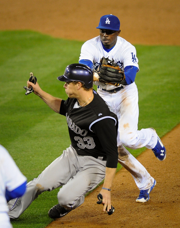 . The Dodgers\' Dee Gordon tags out the Rockies\' Justin Morneau on a double play in the 11th inning, Friday, April 25, 2014, at Dodger Stadium. (Photo by Michael Owen Baker/L.A. Daily News)