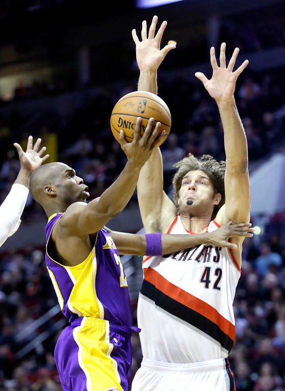 . Los Angeles Lakers guard Jodie Meeks, left, goes to the hoop against Portland Trail Blazers center Robin Lopez during the first half of an NBA basketball game in Portland, Ore., Monday, March 3, 2014. (AP Photo/Don Ryan)