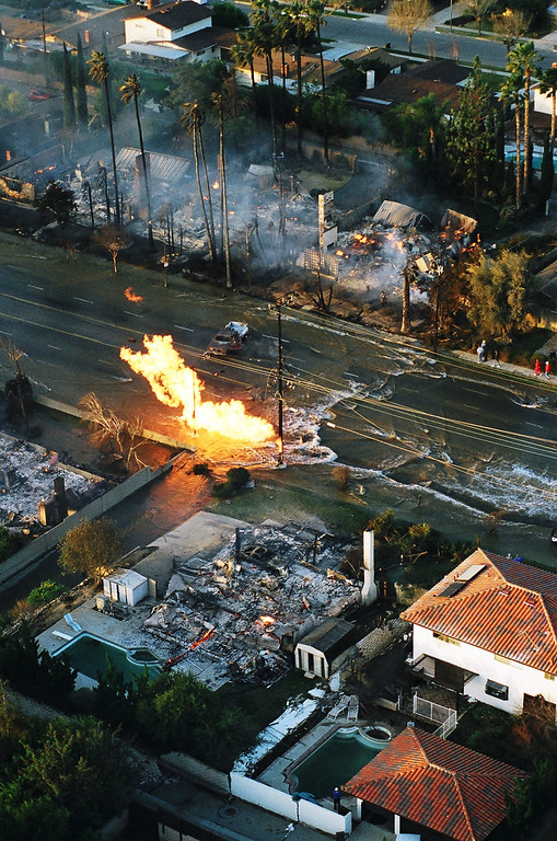 . The scene near Balboa Blvd. and Rinaldi Street as the sun rose on the morning of Jan. 17. Flames from a broken gas line destroyed surrounding homes as water from a ruptured water main flowed down the street.   Los Angeles Daily News file photo