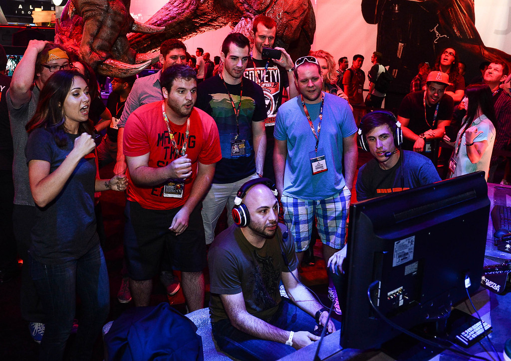 """. Gamers react as they play the video game \""""Evolve\"""" at Electronic Entertainment Expo in Los Angeles on Tuesday, June 10, 2014. (Photo by Watchara Phomicinda)"""
