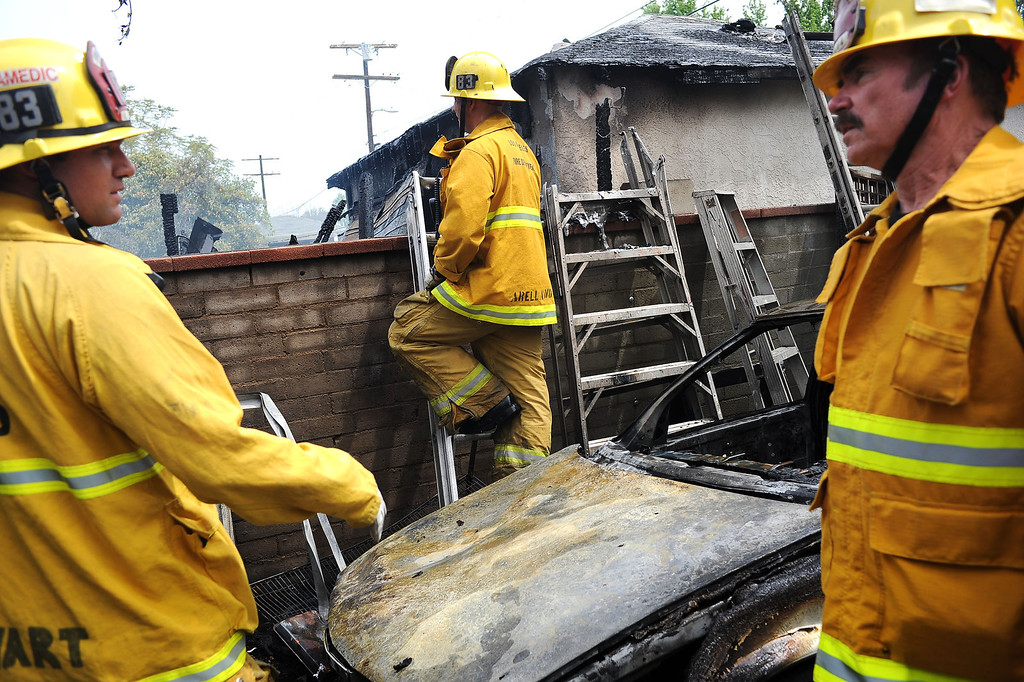 . Firefighters gather in the backyard of a home that was damaged after a fire broke out in the 17800 block of Vanowen St. in Reseda, CA April 10, 2014.(Andy Holzman/Los Angeles Daily News)