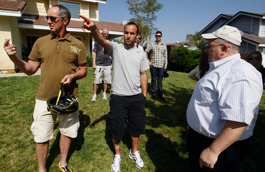 """. Landon Donovan points out where he tossed a newspaper to Rick Reilly, left, and San Bernardino Sun Circulation Manager Lynn Brokaw as they tape a segment for the ESPN show \""""Home Coming with Rick Reilly\"""" in Redlands Monday, April 19, 2010. Donovan, now a professional soccer player with the Los Angeles Galaxy, was a paper boy for the Redlands Daily Facts when he was a young teenager. (Staff file photo/Redlands Daily Facts)"""