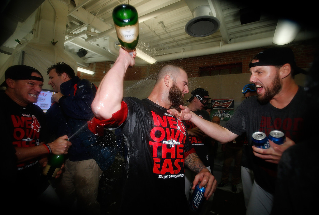 . BOSTON, MA - SEPTEMBER 20: John Lackey #41, Jake Peavy #44, Mike Napoli #12 and  of the Boston Red Sox enjoy some champagne after winning the AL East Division by beating  the Toronto Blue Jays at Fenway Park on September 20, 2013 in Boston, Massachusetts.  (Photo by Jim Rogash/Getty Images)
