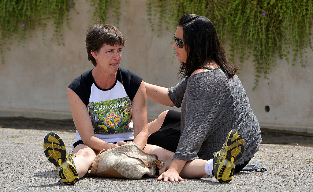 . Laurie McNaughton, left, is comforted by Gami McGuire as McNaughton\'s home burns. The home in the 1600 block of Olive Street, one of the city�s historic neighborhoods, was destroyed in a fire Wednesday April 9, 2014, according to fire officials. As they arrived, firefighters found the home, built in 1903, engulfed in flames and smoke billowing out of the structure. (Photo by Rick Sforza/The Sun)