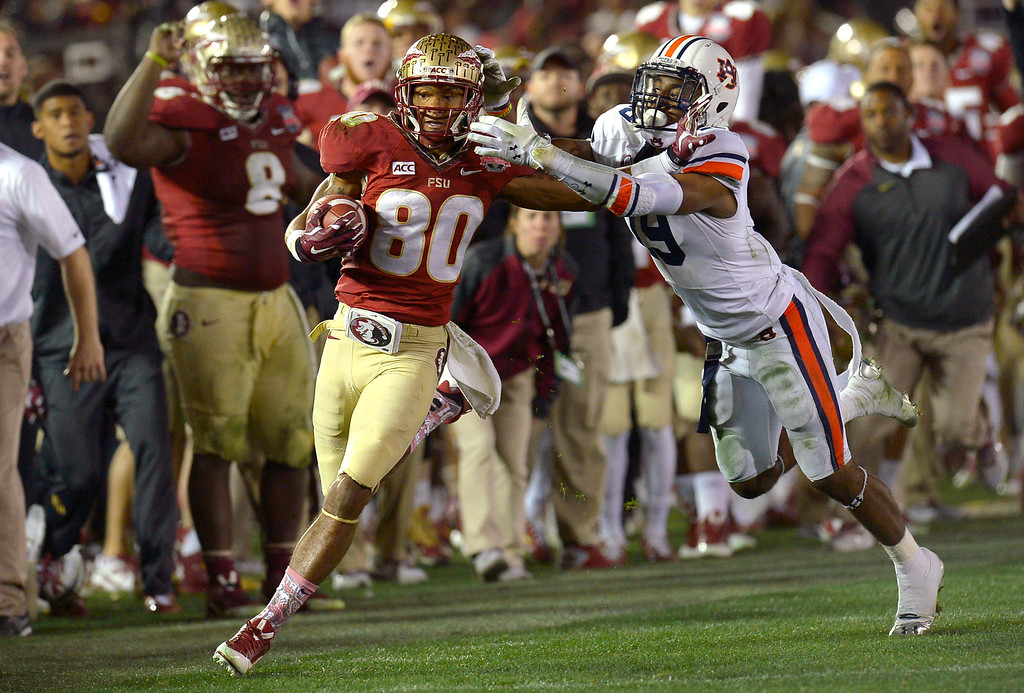 . Florida State\'s Rashad Greene carries tha ball as Auburn\'s Ryan White tries to bring him down during the 2014 Vizio BCS National Championship January 6, 2014 in Pasadena CA.  Florida State won the game 34-31.(Andy Holzman/Los Angeles Daily News)