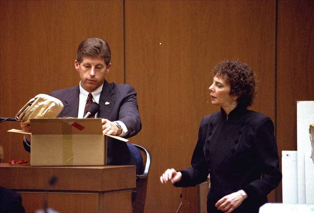 . Los Angeles Police Detective Mark Fuhrman shows the jury in the O.J. Simpson double murder trial evidence found in the white Bronco that prosecutors contend defendant O.J. Simpson drove the night his ex-wife and a friend were murdered, during testimony in Los Angeles Friday, March 10, 1995. Prosecuting attorney Marcia Clark looks on. (AP Photo/Nick Ut, Pool)