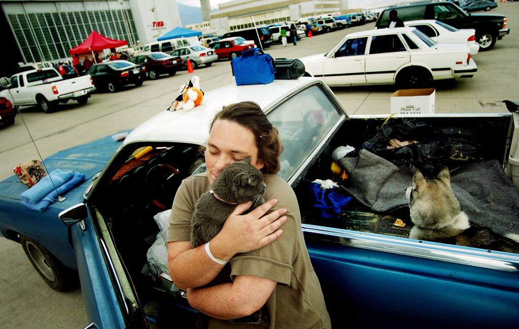 . Ten years ago this month the arson caused Old Fire, fanned by Santa Ana winds burned thousands of acres, destroyed hundreds of homes and caused six deaths. The fire burned homes in San Bernardino, Highland, Cedar Glen, Crestline, Running Springs and Lake Arrowhead and forced the evacuation of thousand of residents. Kimberly Drum, 37, of Crestline hugs her cat, Bunny, on the flightline at San Bernardino International Airport where they evacuated from their home from the Old Fire. Drum, her three kids, dog and cat are all living in a tent outside of the hanger. (Staff file photo/The Sun)