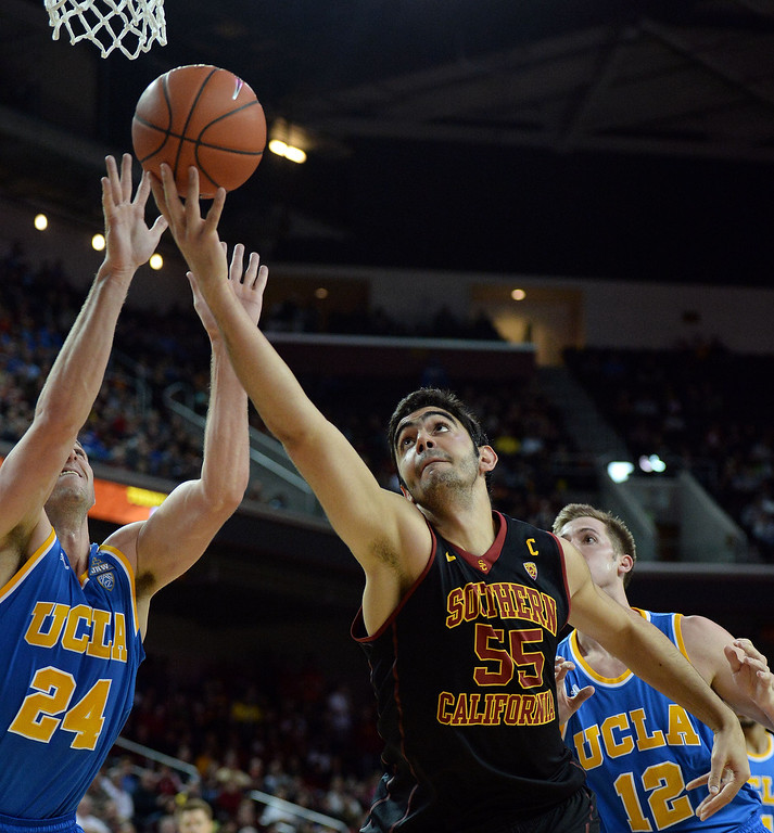 . Southern California\' Omar Oraby (55) drives to the basket past UCLA\'s Travis Wear (24) as David Wear (12) looks on in the second half of a PAC-12 NCAA basketball game at Galen Center in Los Angeles, Calif., on Saturday, Feb. 8, 2014. UCLA won 83-73. (Keith Birmingham Pasadena Star-News)