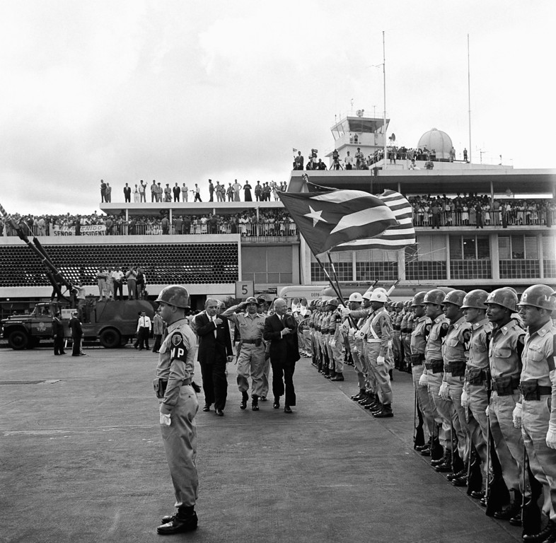. President Eisenhower, center, and Gov. Luis Munoz Marin, left, inspect a unit of the Puerto Rico National Guard at the San Juan airport, Feb. 22, 1960 just after the president\'s arrival. This was the first stop on the President\'s flight to South America. (AP Photo)