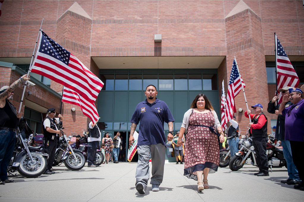 . The Patriot Guard fly flags as Sgt. Luis Bardales, a resident of Irwindale, and his wife Rebecca leave his Purple Heart ceremony at the Army National Guard in Azusa Saturday, July 12, 2014. Bardales was wounded by a roadside IED in Baghdad, Iraq and saved gunner Gabriel Herrera by pulling him out of their Humvee before another IED explosion. (Photo by Sarah Reingewirtz/Pasadena Star-News)