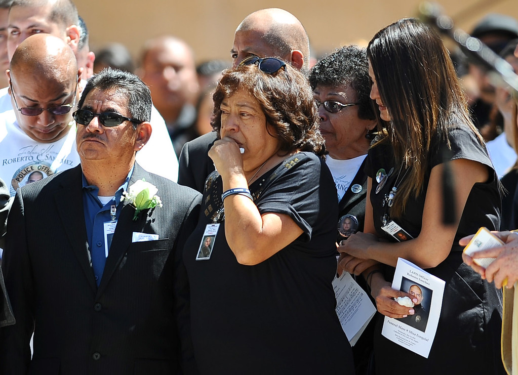 . Parents Francisco and Patricia Sanchez and wife Sonia Sanchez look as LAPD Officer Roberto Sanchez casket is loaded into a hearse following his funeral at the Cathedral of Our Lady of the Angels in Los Angeles, CA May 14, 2014.  Sanchez was killed in a hit-and-run crash involving a SUV driver who is accused of deliberately ramming the officer\'s patrol car in Harbor City.(Andy Holzman/LA Daily News)