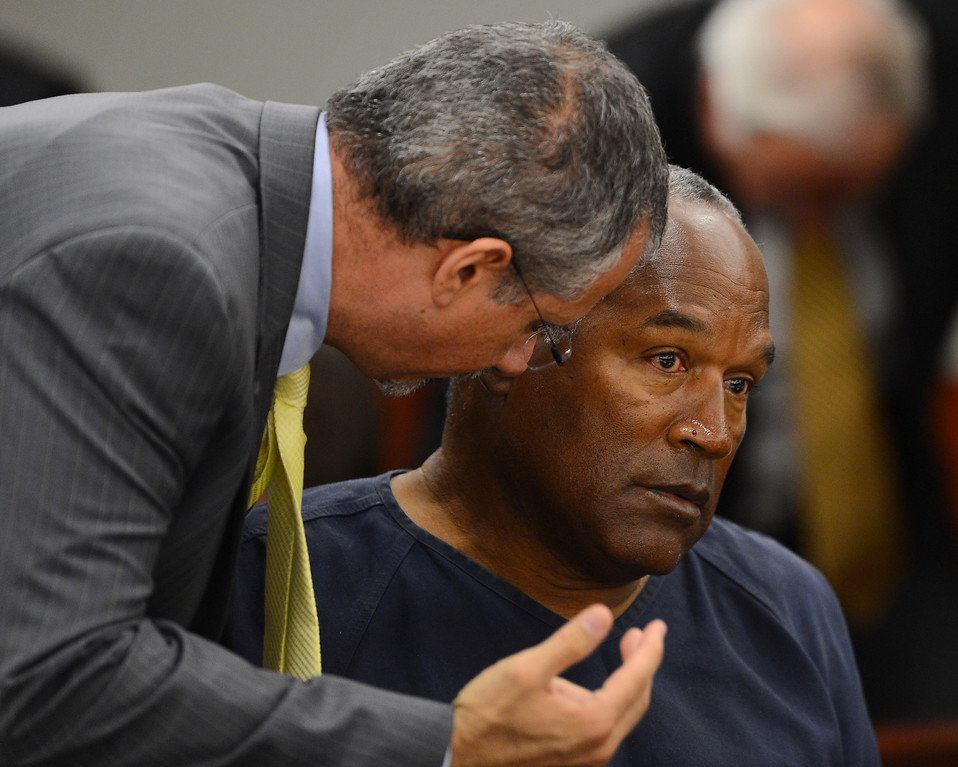 . Defense attorney Ozzie Fumo, left, confers with his client, O.J. Simpson during an evidentiary hearing for Simpson in Clark County District Court on Tuesday, May 14, 2013 in Las Vegas.  The hearing is aimed at proving Simpson\'s trial lawyer, Yale Galanter, had conflicted interests and shouldn\'t have handled Simpson\'s case. Simpson is serving nine to 33 years in prison for his 2008 conviction in the armed robbery of two sports memorabilia dealers in a Las Vegas hotel room. (AP Photo/Ethan Miller, Pool)