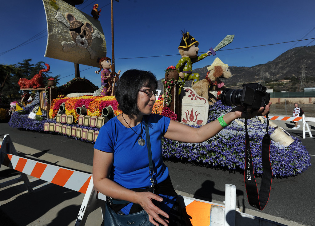 . Lin Wu, a professor at Cal Poly takes a photo of herself in front of the Cal Poly float. The 125th Rose Parade\'s Showcase of Floats was staged on Sierra Madre Boulevard between Washington Boulevard and Sierra Madre Villa Avenue, and Washington Boulevard between Sierra Madre Boulevard and Woodlyn Road.  Pasadena, CA January 1, 2014.(John McCoy/Los Angeles Daily News)