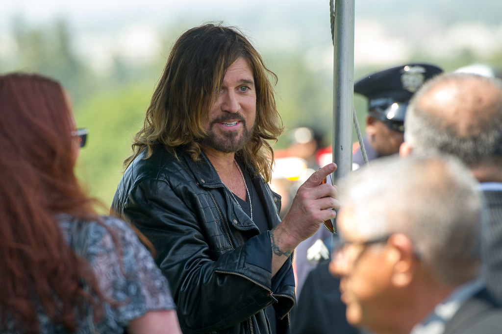 . Singer Billy Ray Cyrus talks to family members of LAPD officer Chris Cortijo, Tuesday, April 22, 2014, at Forest Lawn Hollywood Hills. (Photo by Michael Owen Baker/L.A. Daily News)