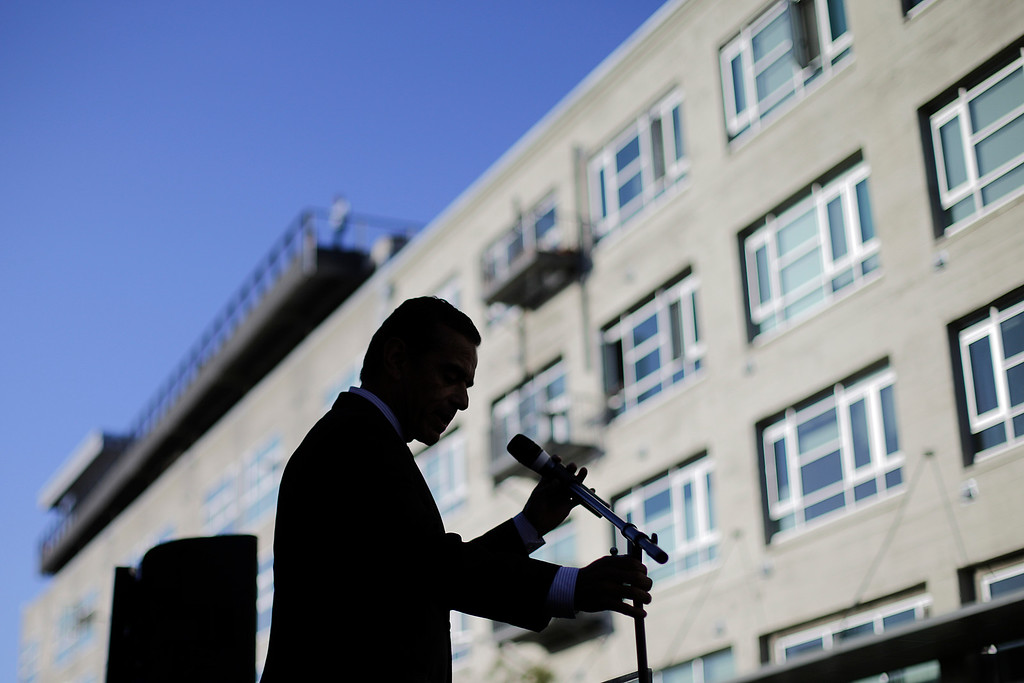 . Los Angeles Mayor Antonio Villaraigosa is silhouetted as he adjusts a microphone stand during a groundbreaking ceremony for the La Kretz Innovation Campus in Los Angeles, Wednesday, June 19, 2013.  (AP Photo/Jae C. Hong)