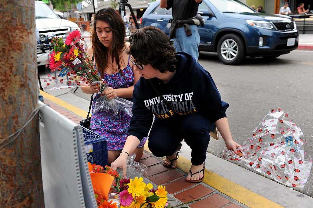 . UCSB students Zadie(cq) Dorotheo, left, and Ashley Eidenier place flowers in front of IV Deli Mart in Isla Vista, Saturday, May 24, 2014, which was one of the scenes of Friday night\'s shootings. (Photo by Michael Owen Baker/Los Angeles Daily News)