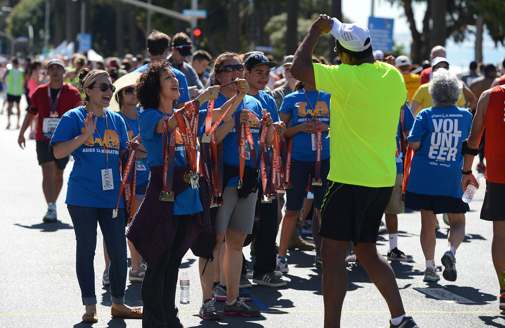 . Runners are rewarded with a medal along Ocean Boulevard,  after crossing the finish line of  2014 ASICS LA Marathon finisher Bill Hopkins after feeling nauseous after he crossed the finish line in Santa Monica Calif,    Sunday, March 9,  2014. 