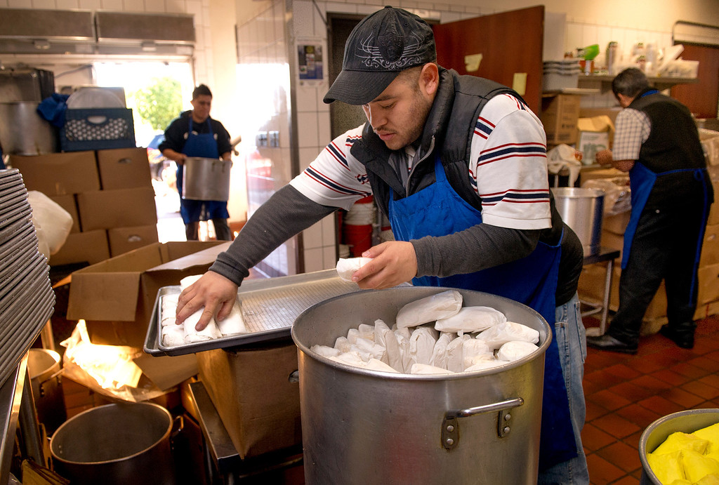 . Raul Campos packs tamales in cooking pots at Tamales Lilianas where thousands of tamales are sold over the Christmas season at their East Los Angeles restaurant located at 4629 East Cesar E. Chavez Ave. Dec. 23, 2013.   (Staff photo by Leo Jarzomb/San Gabriel Valley Tribune)
