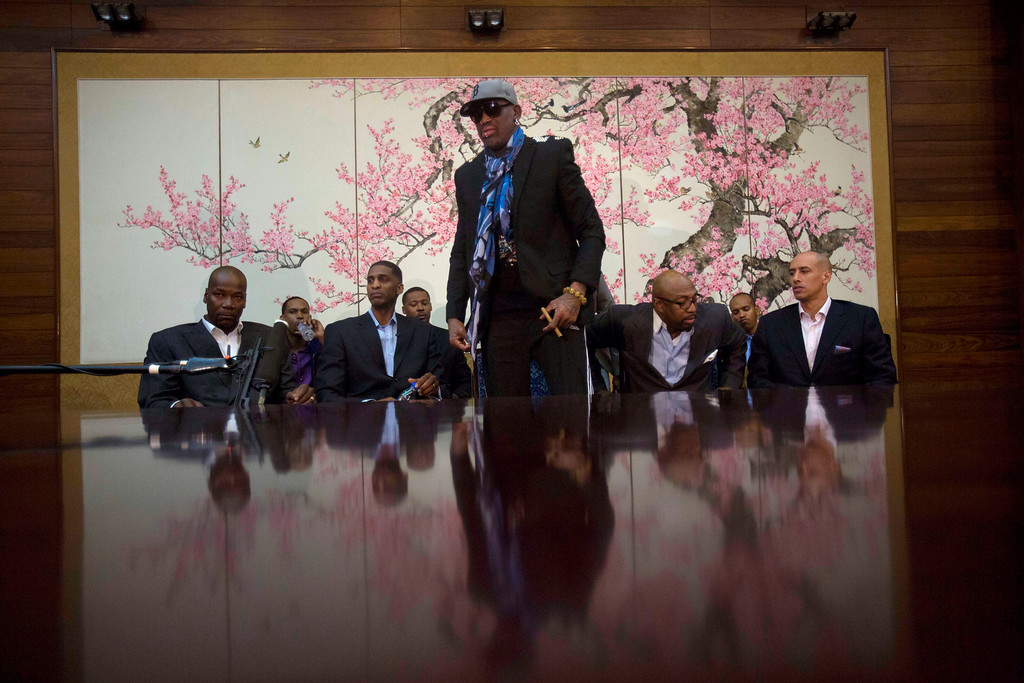 """. Dennis Rodman stands up to leave after he and fellow US basketball players completed a television interview at a Pyongyang, North Korea hotel Tuesday, Jan. 7, 2014. Rodman came to the North Korean capital with a team of USA basketball stars for an exhibition game on Jan. 8, the birthday of North Korean leader Kim Jong Un. From left to right are Cliff Robinson, Jerry Dupree, Charles D. Smith, unidentified, Vin Baker, Andre \""""Silk\"""" Poole and Doug Christie. (AP Photo/David Guttenfelder)"""
