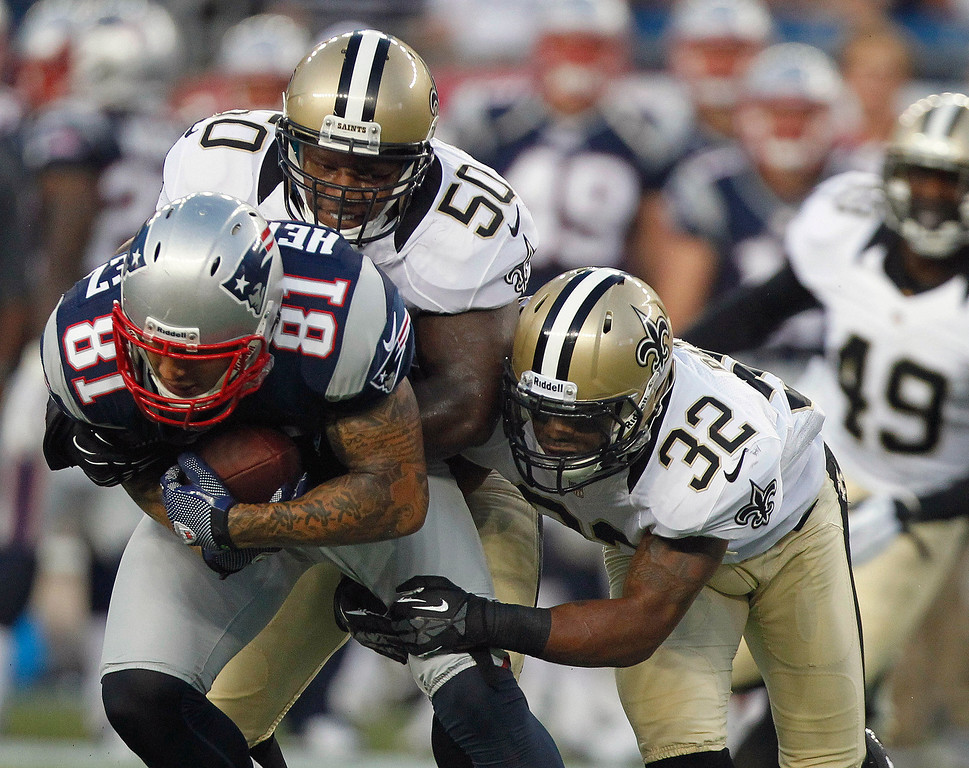 . New England Patriots tight end Aaron Hernandez (81) is wrapped up by New Orleans Saints linebacker Curtis Lofton (50) and defensive back Johnny Patrick (32) during their first NFL preseason football game in Foxborough, Mass., Thursday, Aug. 9, 2012. (AP Photo/Michael Dwyer)