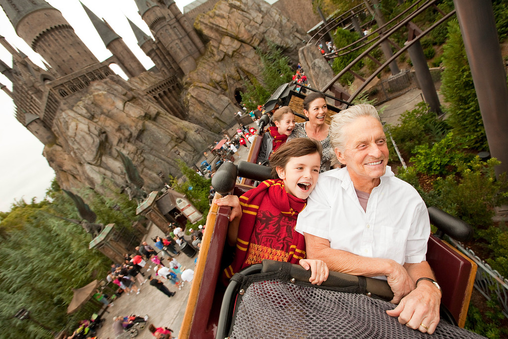 . In this Saturday, Nov. 27, 2010 photo provided by Universal Orlando Resort, Academy Award-winning actors Michael Douglas, right, and wife Catherine Zeta-Jones, second from right, along with their children Dylan, 10, front left, and Carys, 7, pass over The Wizarding World of Harry Potter and Hogwarts Castle, while riding the Flight of the Hippogriff at Universal Orlando Resort in Orlando, Fla. (AP Photo/Universal Orlando Resort, Matt Stroshane)
