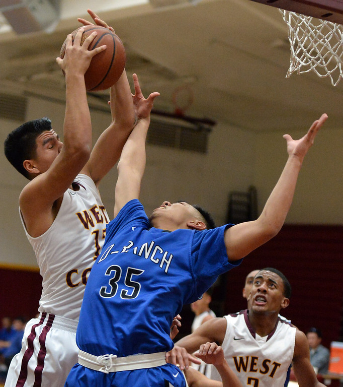 . West Covina\'s Jacob Acosta (12) rebounds past Diamond Ranch\'s Paolo Reorizo (35) in the first half of a prep basketball game at West Covina High School in West Covina, Calif., on Wednesday, Jan. 8, 2014. (Keith Birmingham Pasadena Star-News)