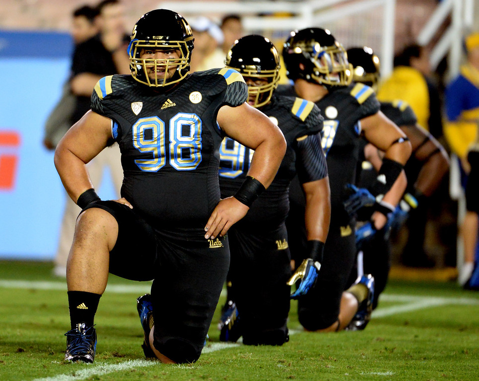 . UCLA Bruins wearing black uniforms with gold trim prior to their college football game against the Washington Huskies in the Rose Bowl in Pasadena, Calif., on Friday, Nov. 15, 2013. 