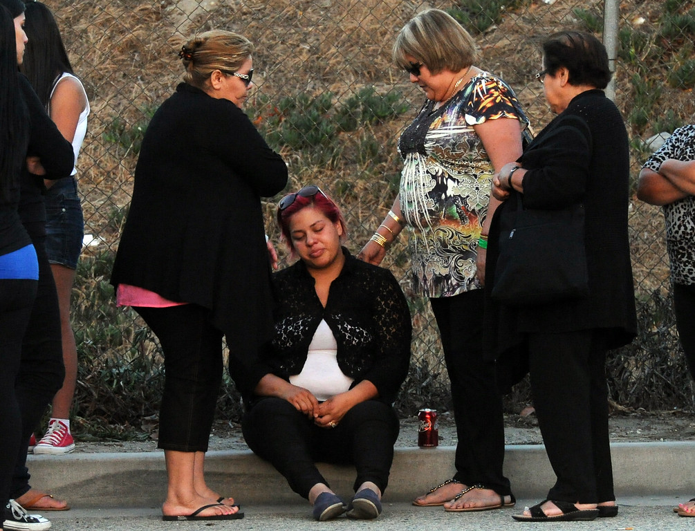 . Myra Velasquez, center, wife of Efren Velasquez is consoled by family and friends in front of a make shift memorial for a Man and two children who were killed in a late Thursday night crash along the 3500 block of San Gabriel River Road on Friday, June 14, 2013 in Industry, Calif. Three others were injured in the crash.  (Keith Birmingham/Pasadena Star-News)