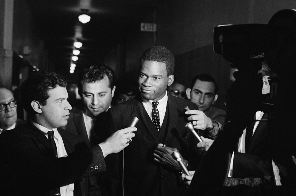 . Lucius Allen, 19-year-old star basketball player for UCLA is questioned by reporters in Los Angeles on May 26, 1967. Allen appeared at Municipal Court today for arraignment on charges of possessing marijuana .With Allen is his attorney Lawrence Moreno, at left behind Allen. Preliminary hearing was set for June 20th and Allen is out on ball. (AP Photo)