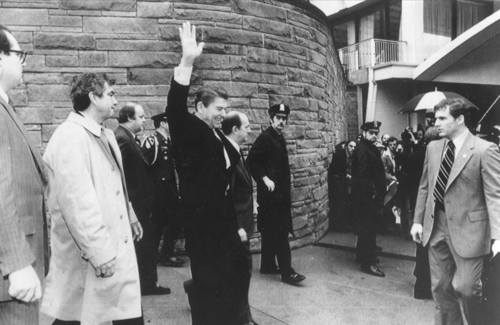 . U.S. President Ronald Reagan waves just before he is shot outside the Washington Hilton, Monday, March 30, 1981.  From left are secret service agent Jerry Parr, in raincoat, who pushed Reagan into the limousine; press secretary James Brady, who was seriously wounded; Reagan; Michael Deaver, Reagan\'s aide; unidentified policeman; Washington policeman Thomas K. Delahanty, who was shot; and secret service agent Timothy J. McCarthy, who was shot in the stomach.  (AP Photo/U.S. White House)