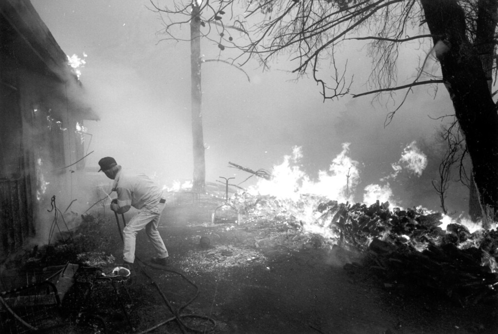 . Jerry Tirrell uses a garden hose to fight the fire at his neighbor\'s home near Mulholland Highway and Stunt Road.  (11/2/93)   Los Angeles Daily News file photo