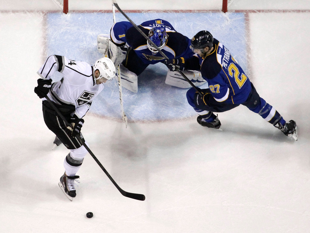 . Los Angeles Kings\' Justin Williams, left, tries to control the puck as St. Louis Blues goalie Brian Elliott and Blues\' Alex Pietrangelo, right, defend during the first period in Game 5 of a first-round NHL hockey Stanley Cup playoff series, Wednesday, May 8, 2013, in St. Louis. (AP Photo/Jeff Roberson)