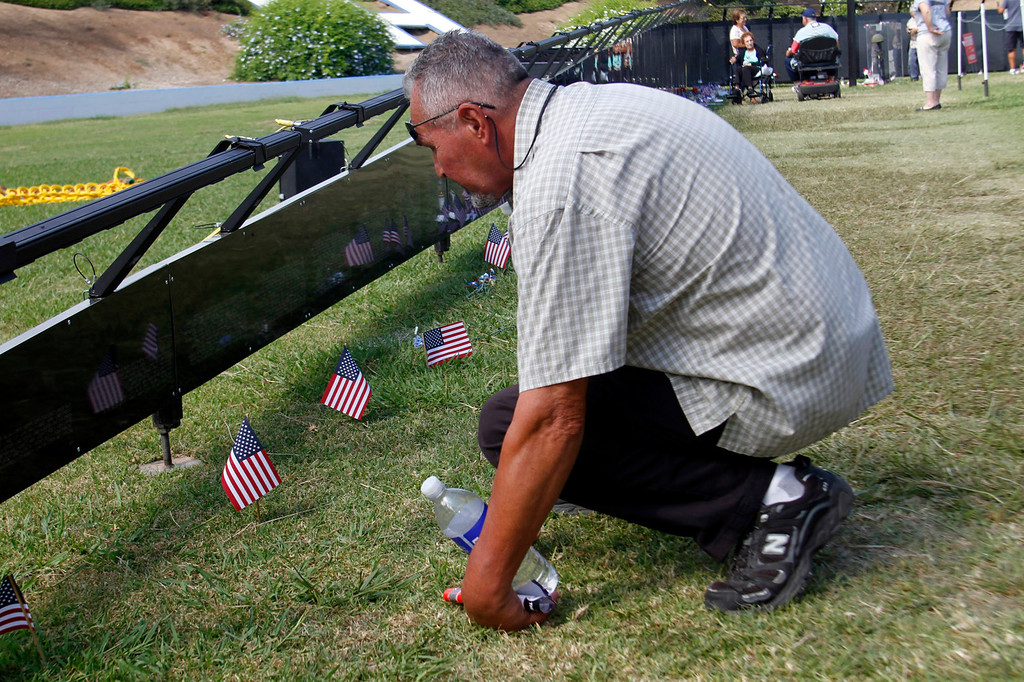 """. Sam Escobar, of La Habra, looks closely for a name on the Vietnam Veterans Memorial, during the Vietnam Veterans Memorial \""""The Wall That Heals\"""" Closing Ceremony event, at La Habra High School, in La Habra, Sunday, July 14, 2013. (SGVN/Correspondent Photo by James Carbone)"""