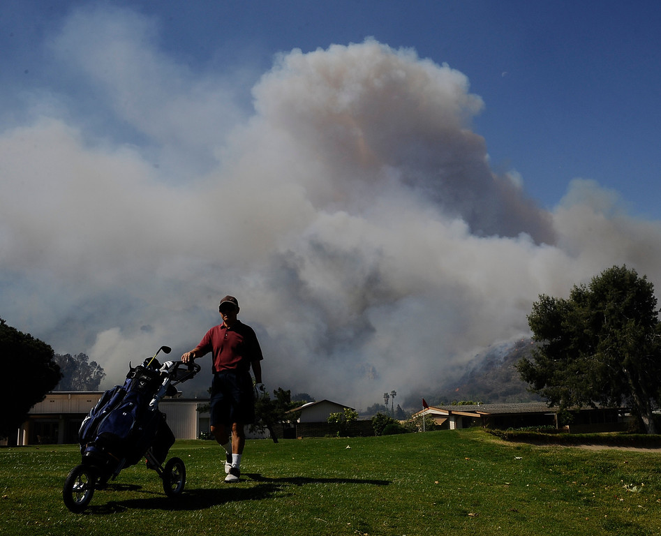 . May 2,2013. Camarillo CA. Golfers continute to play through  as a brush burns through more than 7,000 plus acres in Camarillo, threatening homes and schools as the fire pushes forward toward the coast.  The Ventura County Fire Department said the Springs Fire broke out at 6:45 a.m. Thursday along the 101 freeway, 50 miles west of downtown Los Angeles, and has damaged a storage facility as well as some homes.   Photo by Gene Blevins/LA DailyNews