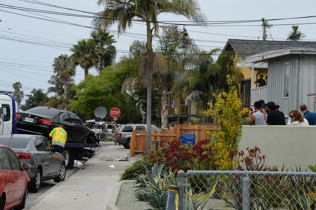 ". Residents watch on May 24, 2014, as a suspected gunman\'s car is removed after a drive-by shooting in Isla Vista, California, a beach community next to the University of California Santa Barbara. Seven people, including the gunman, were killed and seven others wounded in the May 23 mass shooting, Santa Barbara County Sheriff Bill Brown said Saturday. Brown said at a pre-dawn press conference that the shooting in the town of Isla Vista ""appears to be a mass murder situation.\"" Driving a black BMW, the suspect opened fire on pedestrians from his vehicle at several locations in the town.            (ROBYN BECK/AFP/Getty Images)"