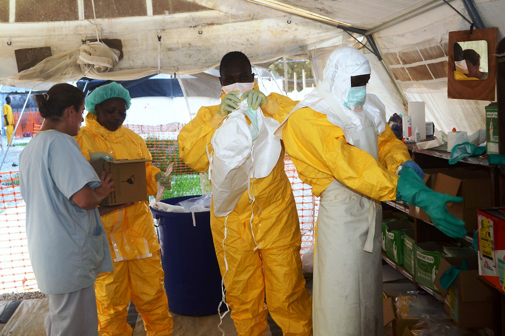 . A picture taken on June 28, 2014 shows members of Doctors Without Borders (MSF) putting on protective gear at the isolation ward of the Donka Hospital in Conakry, where people infected with the Ebola virus are being treated. The World Health Organization has warned that Ebola could spread beyond hard-hit Guinea, Liberia and Sierra Leone to neighbouring nations, but insisted that travel bans were not the answer. To date, there have been 635 cases of haemorrhagic fever in Guinea, Liberia and Sierra Leone, most confirmed as Ebola. A total of 399 people have died, 280 of them in Guinea.         (CELLOU BINANI/AFP/Getty Images)