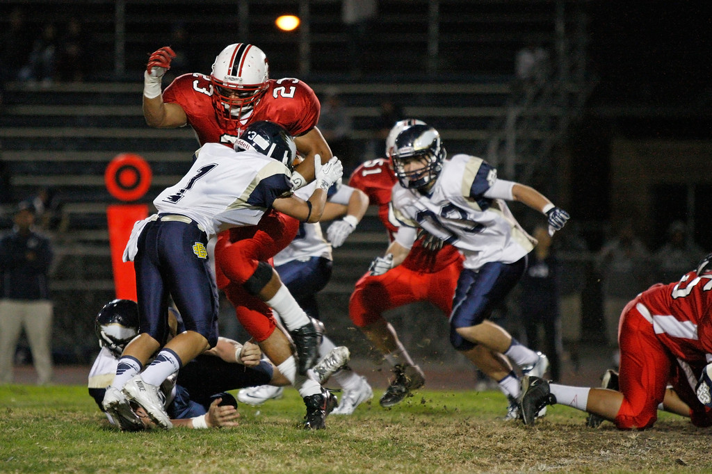 . Running back Will Self #23 of Lawndale is tackled by defensive back Elijah Hale #1 of El Segundo in a Pioneer League matchup at Leuzinger High School on Friday, October 11, 2013 in Lawndale, Calif.  (Michael Yanow / For the Daily Breeze)
