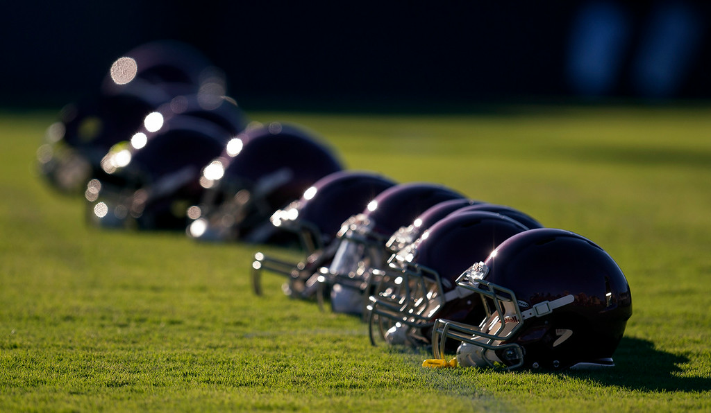 . Football helmets lined up on the field during practice at USC, Howard Jones Field on the USC campus in Los Angeles, Monday, August 4, 2014. (Photo by Hans Gutknecht/Los Angeles Daily News)