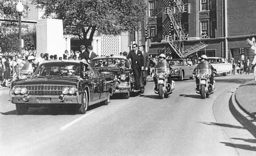 . Seen through the limousine\'s windshield as it proceeds along Elm Street past the Texas School Book Depository, President John F. Kennedy appears to raise his hand toward his head within seconds of being fatally shot in Dallas, Nov 22, 1963. Mrs. Jacqueline Kennedy holds the president\'s forearm in an effort to aid him. Gov. John Connally of Texas, who was in the front seat, was also shot. (AP Photo/James W. (Ike) Altgens)