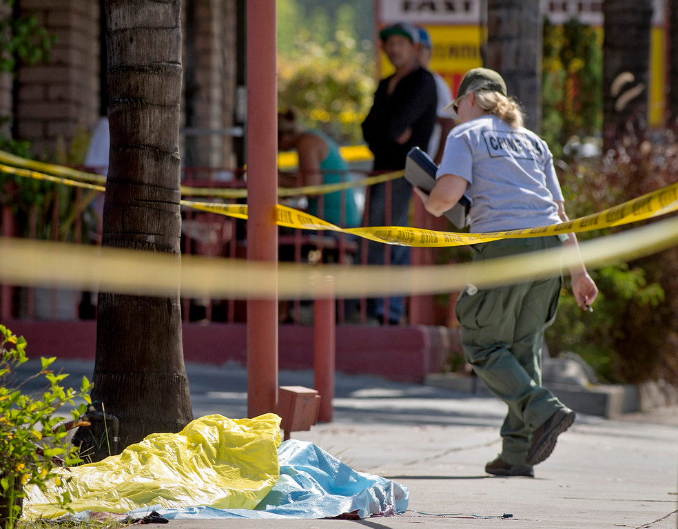 . A crime scene investigator looks over a double homicide that left two homeless men stabbed to death at a car wash at Route 66 and Vermont Avenue in Glendora August 15, 2013.  The two men were sleeping overnight at the car wash when the stabbing occurred about 2 a.m.   (SGVN/Staff photo by Leo Jarzomb)