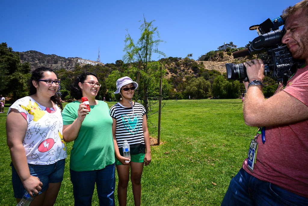""". Yesenia Morales of Los Angeles, with her daughters Scarlett Castro and Sara Morales are interviewed by TV after Morales found a stash of \""""hidden cash\"""" ($80.00) at Lake Hollywood Park Sunday morning, June 1, 2014.   The Hidden cash has been turning up for the last couple of days around Los Angeles.  According to the @hiddencash twitter there will be one more drop in LA Sunday.  ( Photo by David Crane/Los Angeles Daily News )"""