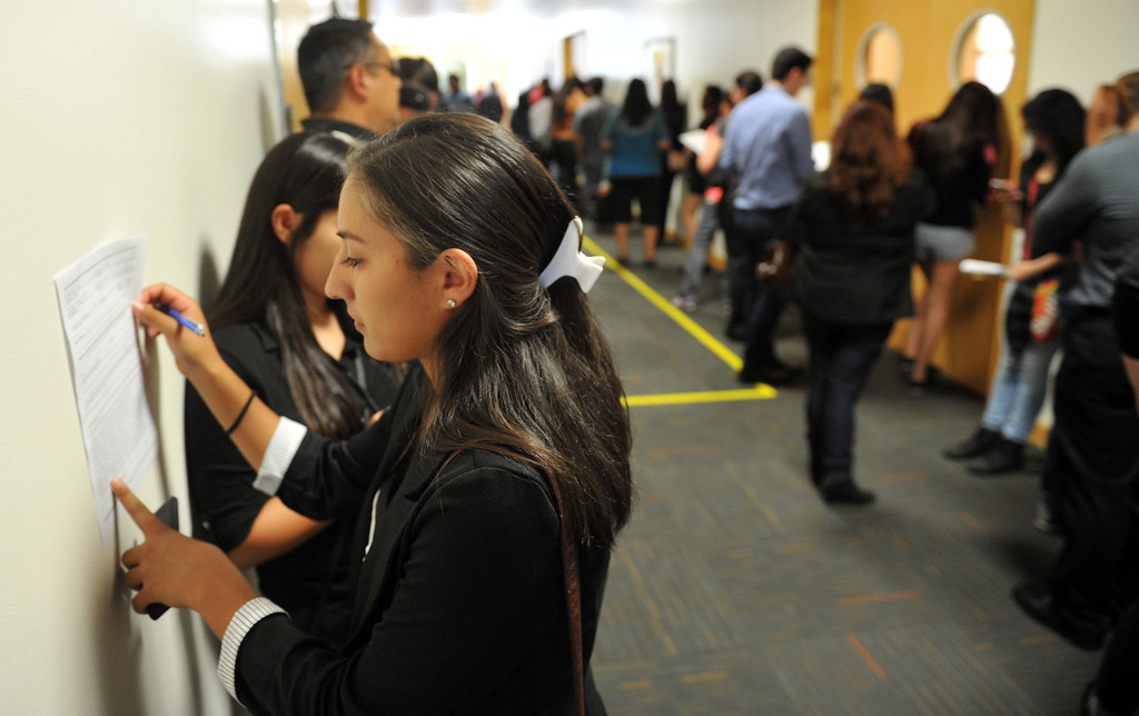 . Raynebeau Barragan,of Los Angeles, fills out an application during a hiring event at Pico Park for the new Norm\'s Restaurant in Pico Rivera on Friday  May 2, 2014. Over 1,000 people are expected to fill out applications for the Pico Rivera Norms that will open on May 22nd.  (Staff Photo by Keith Durflinger/Whittier Daily News)