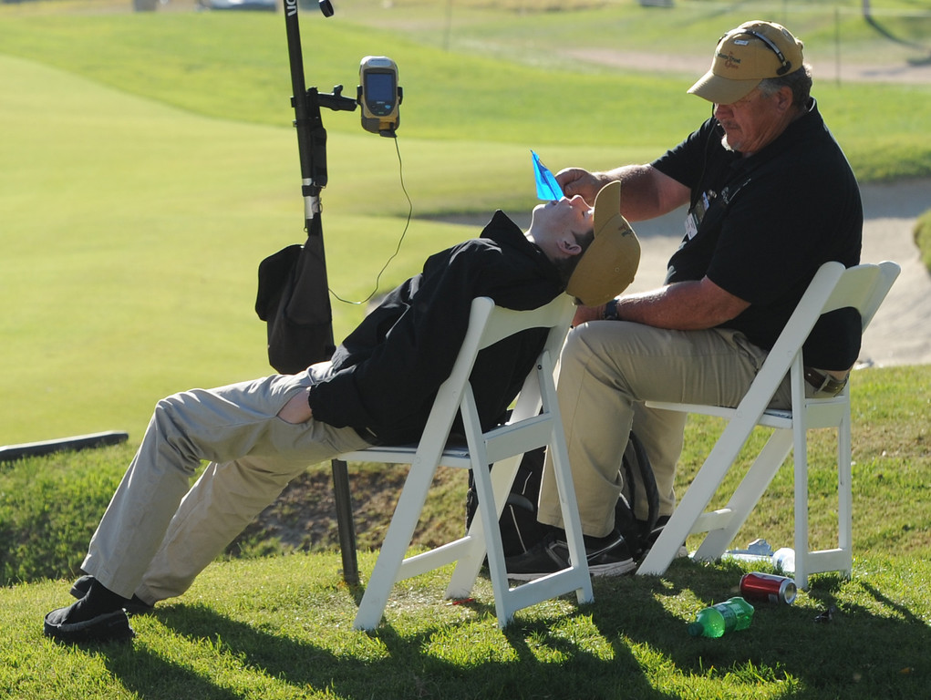. Greg VanHofwegen uses a flag marker to wake up his son Arie. The pair were doing Shot Link duties on the 7th fairway during the second round of the Northern Trust Open. Pacific Palisades, CA. February 13, 2014 (Photo by John McCoy / Los Angeles Daily News)