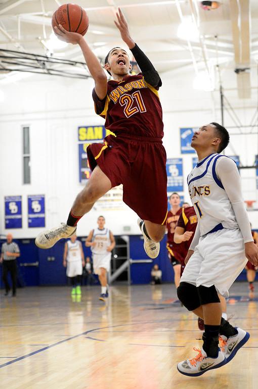 . Wilson\'s Kevin Price (21) goes for a layup as San Dimas\' Ryan Ocampo (1) attempts to stop him as Wilson defeats San Dimas 45-43 Friday night, January 10, 2014 at San Dimas High School.  (Photo by Sarah Reingewirtz/Pasadena Star-News)